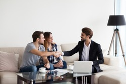Young couple, family at meeting with realtor, interior designer, decorator, landlord making deal. Husband handshaking with man in suit. Concept of meeting with client, customer