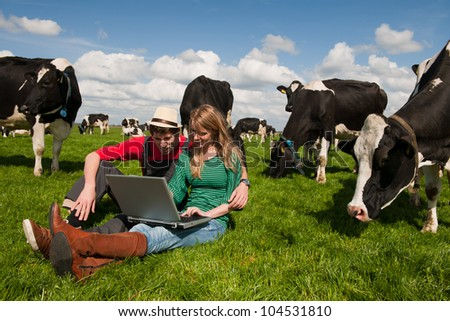 Young couple farmers in farm field with laptop and black and white cows