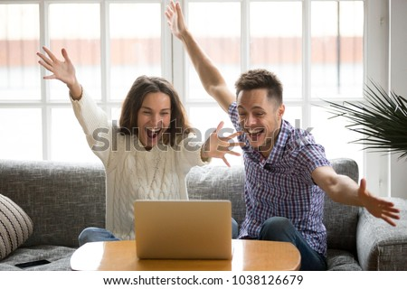 Young couple feeling excited by online win looking at laptop screen, happy man and woman celebrating victory watching video, screaming enjoying good news, motivated by achievement or great result