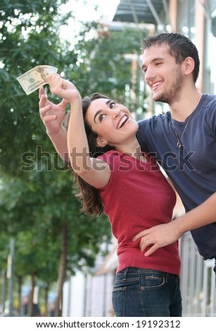 Young couple fighting over couple, finances, outdoor setting.