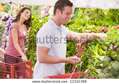 Young couple flirting in supermarket aisle - stock photo