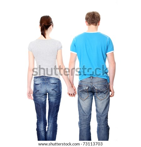 Young couple from behind, holding hands