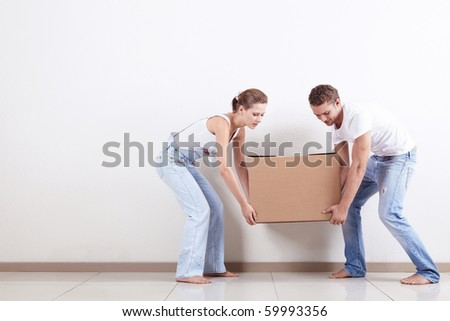 Young couple gently drags a box