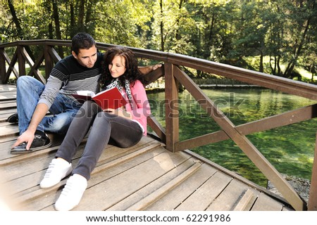 Young couple, girl and boy sitting in park and reading a book