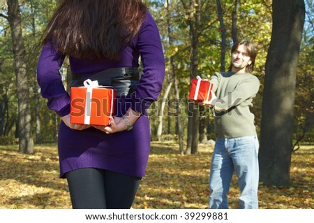 young couple gives gifts, in the autumn park