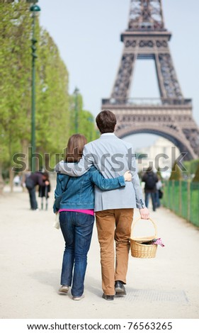 Young couple going to have a picnic by the Eiffel Tower