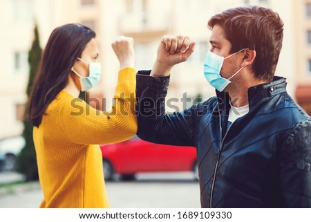 Young couple greetings with elbows outdoors. Woman and man wearing face mask outdoors. Friends shaking elbows outdoors. Don't shake hands. Elbow greeting style. Greeting with elbows.
