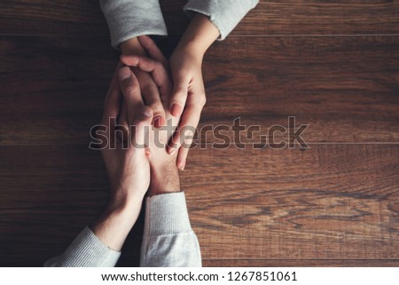 young couple hand on wooden table