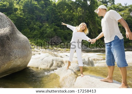 Young couple have a fun time near mountain river