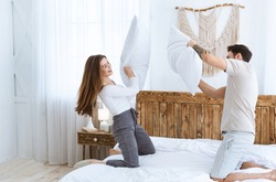 Young couple have fun in bedroom and fights pillows on wooden bed at interior