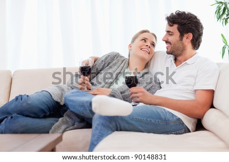 Young couple having a glass of red wine in their living room