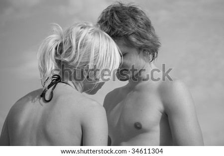 Young couple having a happy silent moment at the beach, black and white