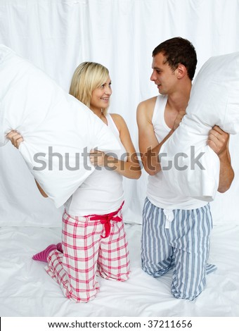 Young couple having a pillow fight in bedroom