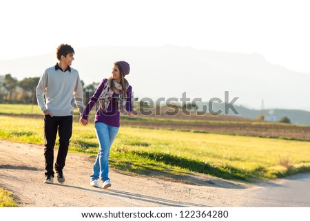 Young couple having a walk on dirt road in countryside