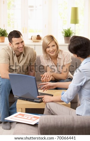 Young couple having appointment with estate agent in sunny living room.?