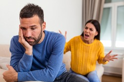 Young couple having argument - conflict, bad relationships. Angry fury woman. Angry young couple sit on couch in living room having family fight or quarrel suffer from misunderstanding