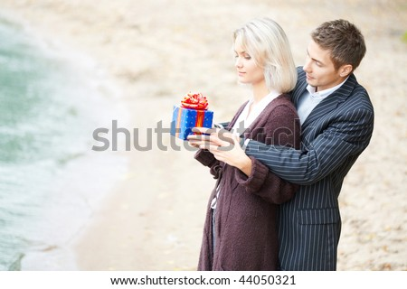 Young couple having fun at beach. They smiling. Gift-box is in their hands.