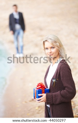 Young couple having fun at the beach. Girl holding a gift. Boyfriend walking on a background. Focus on a girl.