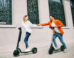 Young couple having fun driving electric scooter through the city