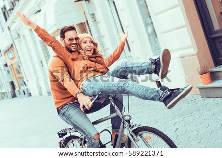 Young couple having fun in the city.Happy young couple going for a bike ride on a autumn day in the city. #589221371