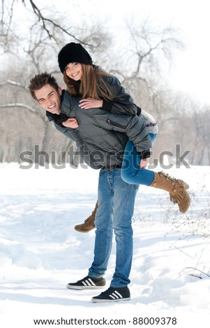 young couple having fun in the park, in winter holidays - stock photo