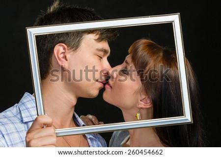 Young couple having fun making faces through tablet frame