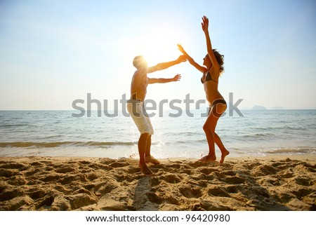 Young couple having fun on a tropical beach at sunset #96420980
