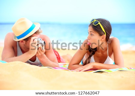 Young couple having fun on beach with vintage retro camera. Funky young interracial couple playful on beach during summer holidays travel vacation. Caucasian man and Asian girl making funny face.