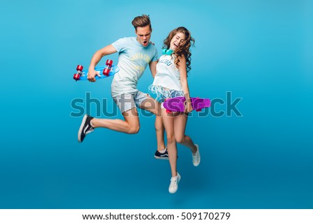 Young couple having fun on blue background in studio. They wear T-shirts, jeans shorts. They are jumping with skateboards in hands.