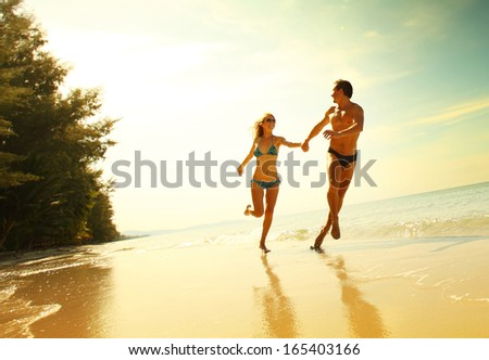Young couple having fun on the tropical beach at sunny day