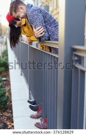 Young couple having fun outdoors balancing on a metal railing on a walkway looking down at their toes poking through the bars with a smile #376128829