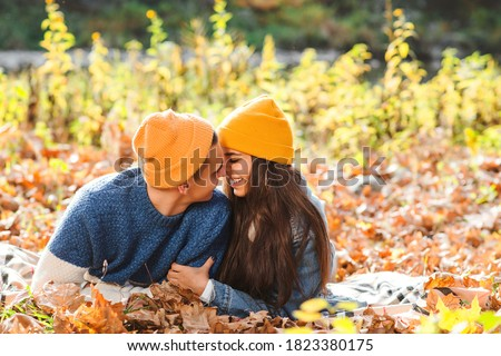 Young couple having fun together in autumn. Love. Fashionable couple enjoying autumn. Fashion, lifestyle and autumn vacation. Stylish man and woman lying among autumn leaves. First kiss. Photo stock ©