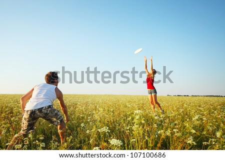 Young couple having fun with a disc on a summer meadow