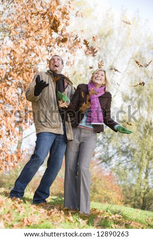 Young couple having fun with autumn leaves in garden
