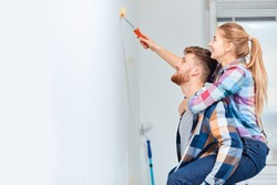 Young couple, having no many for professional painter and ladder, making fun, as a young woman piggybacking on her husband to gain extra height when painting the wall at their home