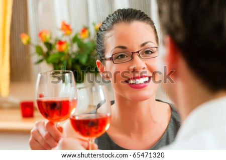 Young couple having romantic dinner - both drinking rose wine