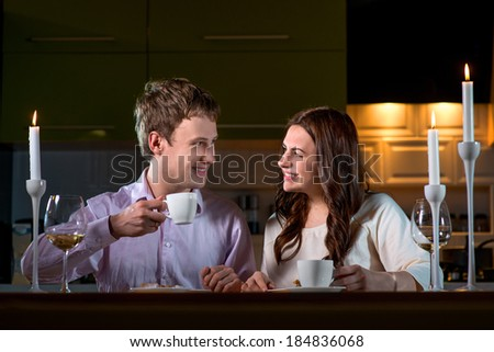 Young couple having romantic dinner on the dinner table at home with candle light