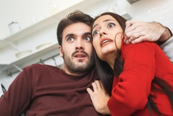 Young couple having romantic evening at home together watching horror scared