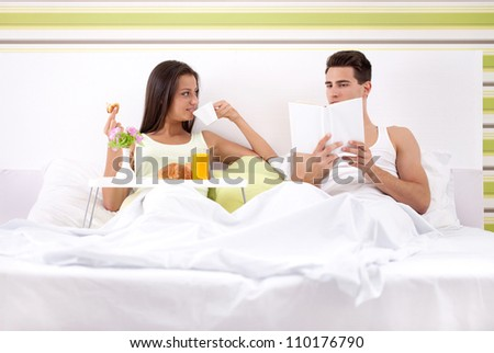 young couple having Sunday morning in bed