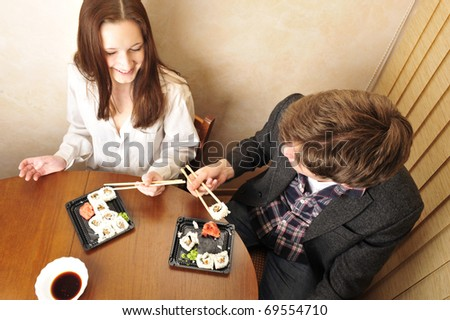 Young couple having supper after hard day at their apartment