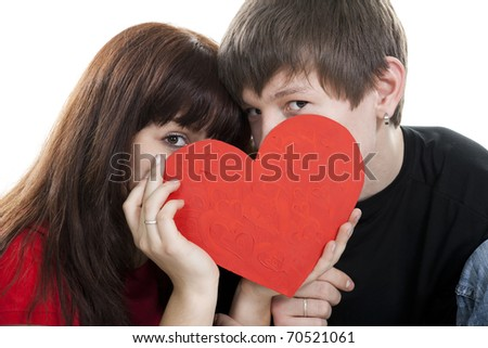 young couple hide by red heart isolated on white