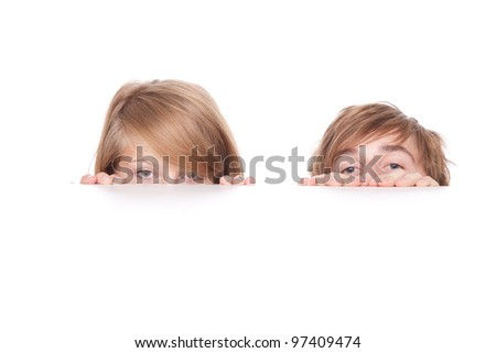 young couple hiding behind and peeking behind the white table