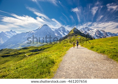 Young couple hiking in panorama trail leading to Kleine Scheidegg from Mannlichen with Eiger, Monch and Jungfrau mountain (Swiss Alps) in the background, Berner Oberland, Grindelwald, Switzerland.