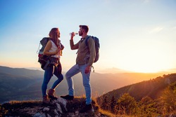 Young Couple Hiking On The Peak of Mountain drinking water