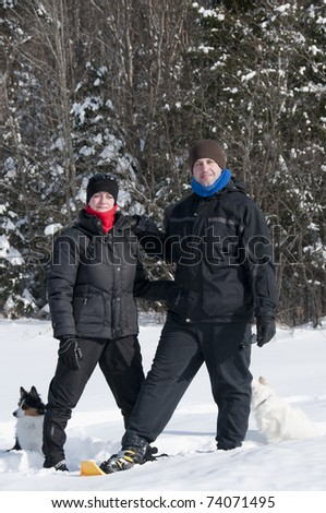 young couple hiking with snowshoes and puppies - stock photo