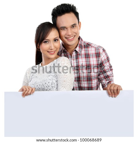 Young couple holding blank banner isolated over white background - stock photo