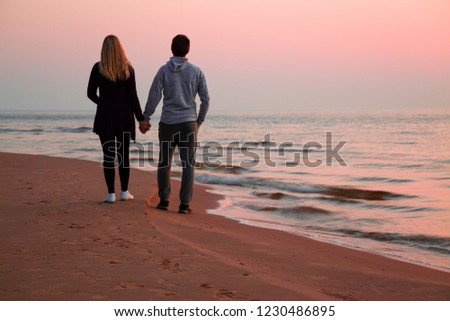 Young couple holding each other hands and walking on sand. Small waves of sea and pink sunset light. Peaceful atmosphere in summer evening. Back view. Empty place for romantic text, quote or sayings.