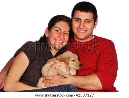 young couple holding golden retriever puppy - stock photo