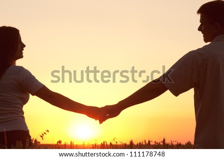 Young couple holding hands and looking at each other on sunny summer day.