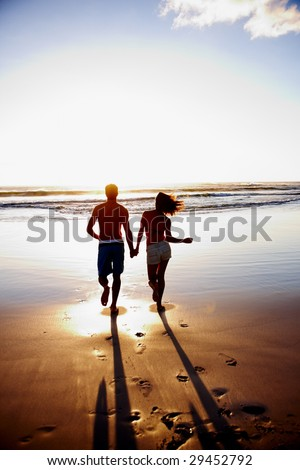 Young couple holding hands and running towards the sea